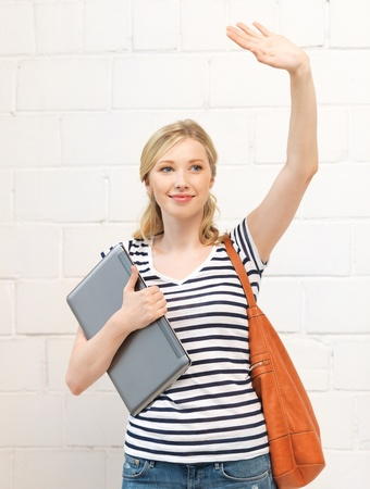happy teenage girl waving a greeting with laptop Stock Photo - 14570028