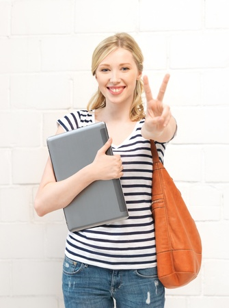 picture of smiling teenage girl with laptop showing victory sign Stock Photo - 14569762