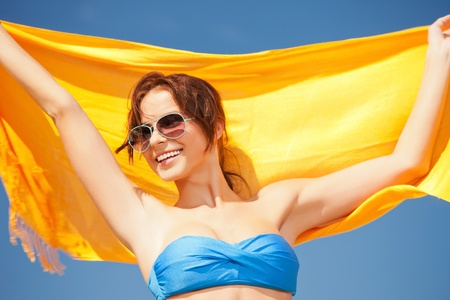 picture of happy woman with yellow sarong on the beach  photo
