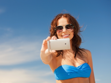 e pretty: picture of happy woman with phone on the beach