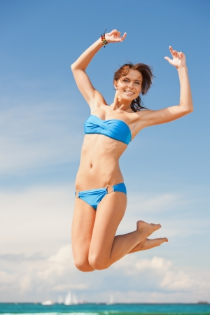 bright picture of happy jumping woman on the beach  photo