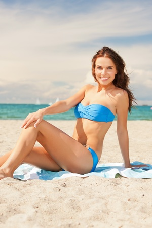 picture of happy smiling woman sitting on a towel  photo