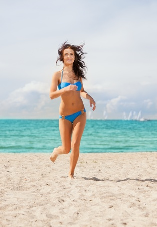 picture of happy smiling woman jogging on the beach  photo