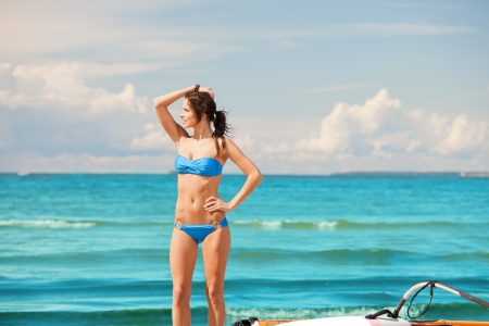 picture of happy woman with wind surf on the beach  photo