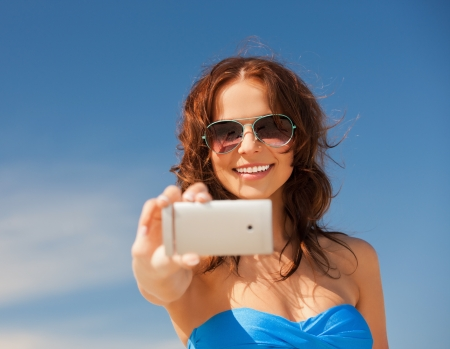 picture of happy smiling woman using phone camera   photo