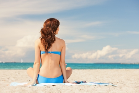 sit shape: picture of woman practicing yoga lotus pose on the beach