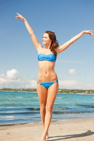 perfect fit: picture of happy smiling woman walking on the beach