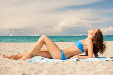 woman laying: picture of happy smiling woman laying on a towel Stock Photo