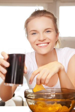 picture of smiling teenage girl with chips and coke photo