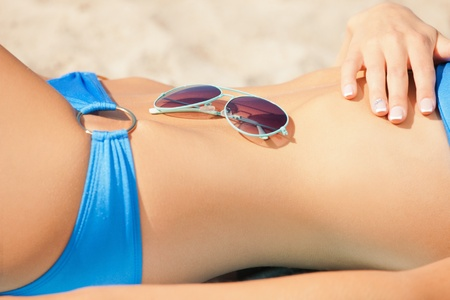 closeup picture of female belly, bikini and shades  photo