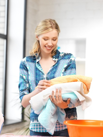 ware house: bright picture of lovely housewife with towels  Stock Photo