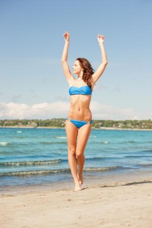 Foto de mujer sonriente feliz caminando en la playa Foto de archivo