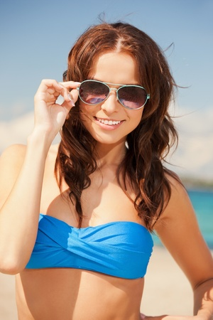 picture of happy woman in sunglasses on the beach  photo