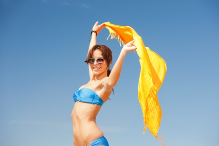Foto de mujer feliz con pareo amarillo en la playa photo