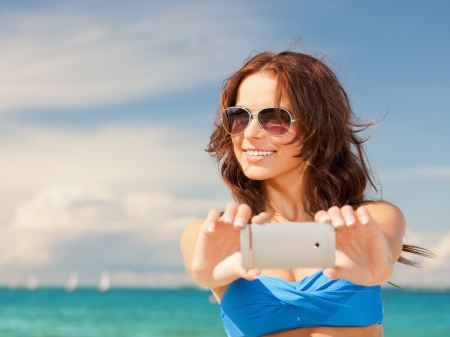 picture of happy woman with phone on the beach  photo