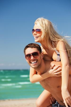 casal: imagem de casal feliz em óculos de sol na praia foco no homem