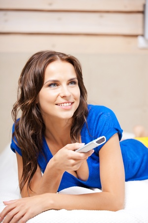 cable tv: bright picture of happy woman with TV remote Stock Photo