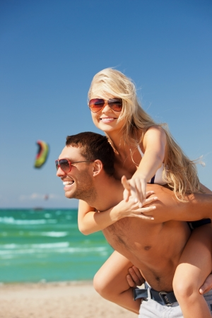 picture of happy couple in sunglasses on the beach   focus on woman  photo