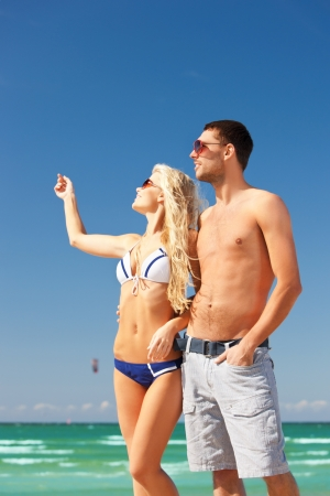 picture of happy couple in sunglasses on the beach  focus on man  photo