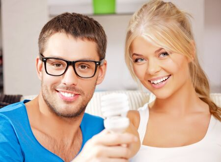 bright picture of happy couple holding energy saving bulb photo