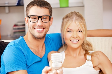 bright picture of happy couple holding energy saving bulb  focus on man  photo
