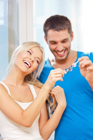 bright picture of happy couple with keys  focus on woman  photo
