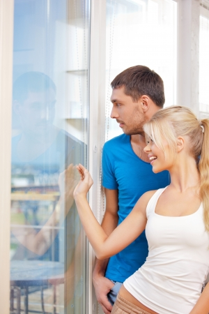 picture window: bright picture of happy couple at the window  focus on man  Stock Photo