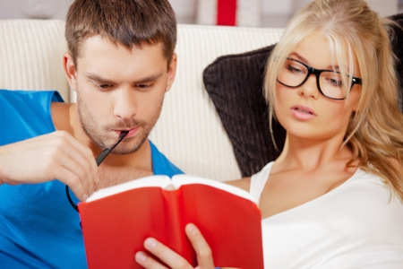 nice looking: bright picture of couple at home with book Stock Photo