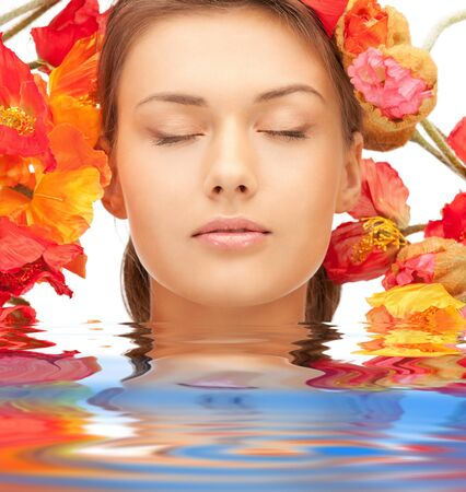lovely woman with red flowers in water photo