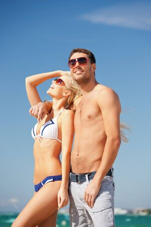 sexy couple on beach: picture of happy couple in sunglasses on the beach  focus on man