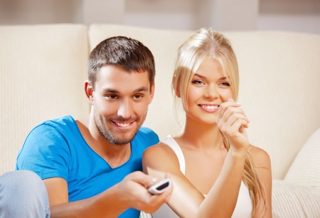 picture of happy romantic couple with TV remote  focus on man  photo