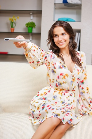 home cinema: bright picture of happy woman with TV remote Stock Photo