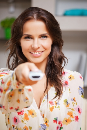 bright picture of happy woman with TV remote Stock Photo