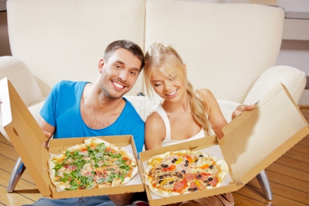 picture of happy romantic couple eating pizza at home photo