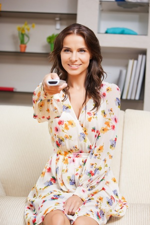 bright picture of happy woman with TV remote Stock Photo - 15501315