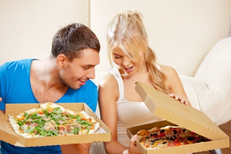 picture of happy romantic couple eating pizza at home  focus on man  photo