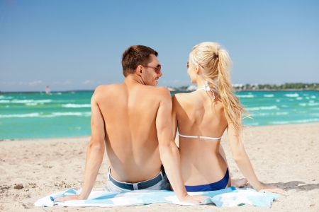 picture of happy couple sitting on the beach  photo