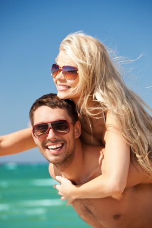 tan woman: picture of happy couple in sunglasses on the beach  focus on man  Stock Photo