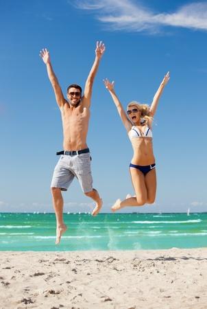 personas saltando: imagen de una pareja feliz saltando en la playa