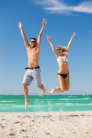 leaping: picture of happy couple jumping on the beach