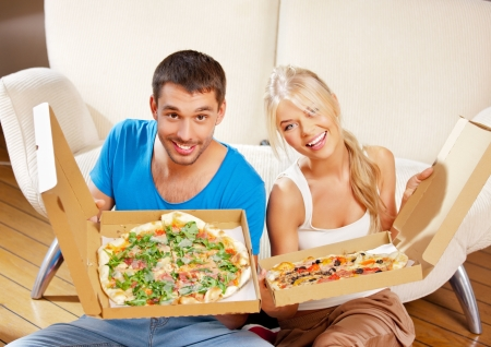 woman eat: picture of happy romantic couple eating pizza at home Stock Photo