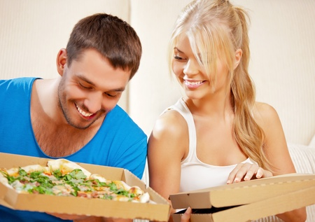 picture of happy romantic couple eating pizza at home  focus on woman  photo