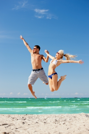 guy on beach: picture of happy couple jumping on the beach  focus on man