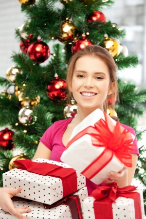 bright picture of happy woman with gift box and christmas tree