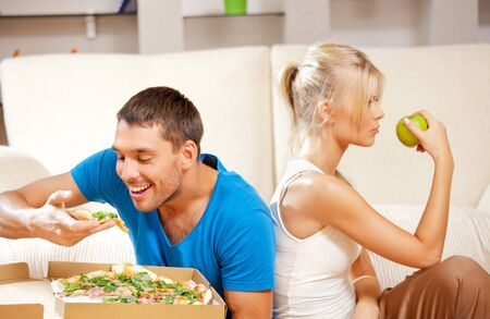 bright picture of couple eating different food  focus on man  Stock Photo - 15361757