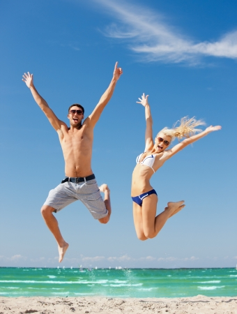 sea sports: picture of happy couple jumping on the beach  focus on man