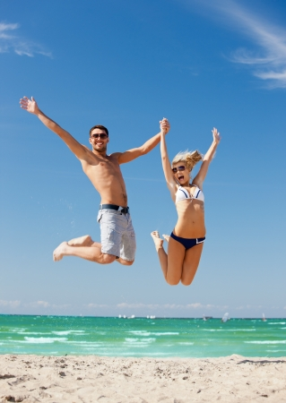 picture of happy couple jumping on the beach