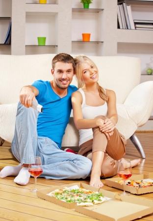 pareja comiendo: imagen de la feliz pareja rom�ntica con mando a distancia Foto de archivo