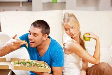 the calories: bright picture of couple eating different food  focus on man  Stock Photo
