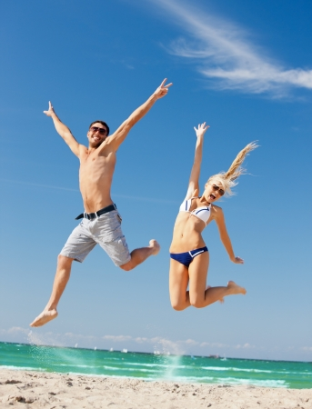 fit man: picture of happy couple jumping on the beach  focus on woman